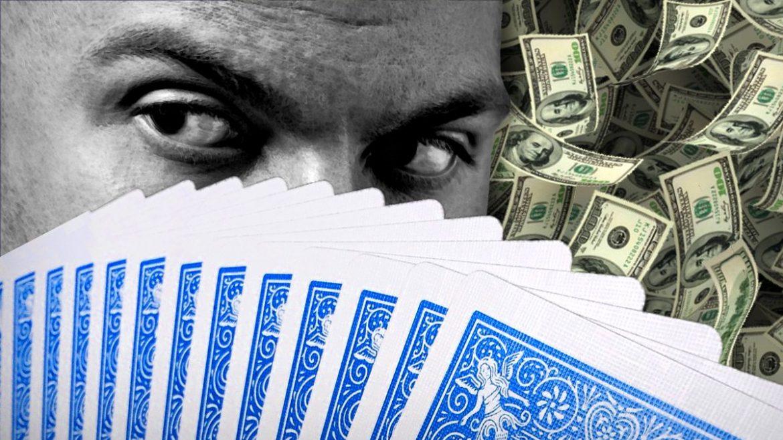 Man Looking Sideways Behind Fan of Cards